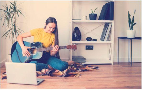 chica joven aprendiendo a tocar la guitarra