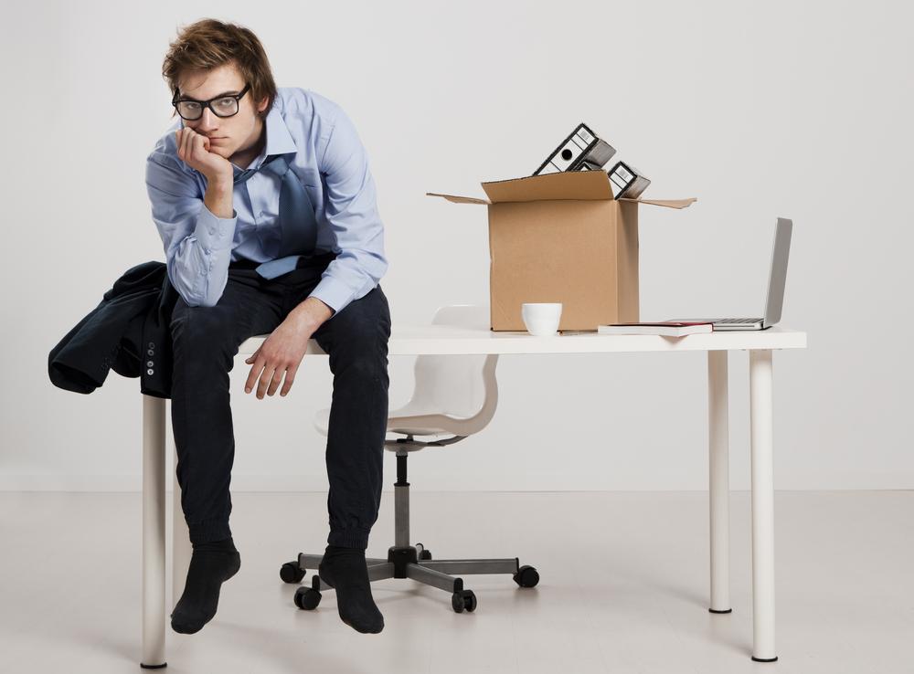 hombre joven desempleado sentado en escritorio después de despido