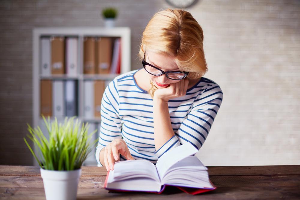 mujer rubia leyendo un libro de género literario