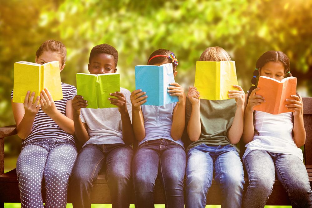 niños en un parque leyendo libros del genero literario comedia y poesía