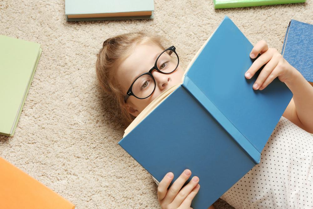 niña acostada leyendo
