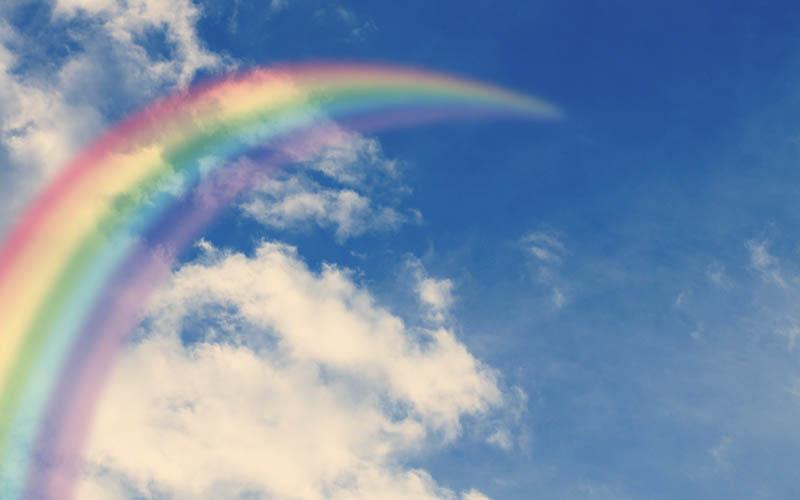 arcoíris sobre cielo azul y despejado)