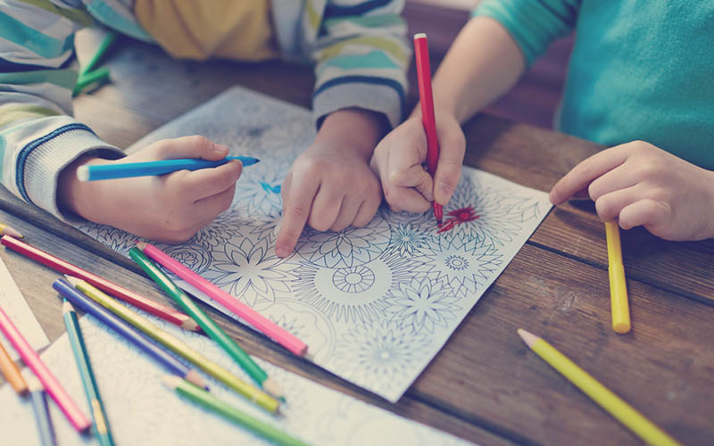 juego de niños coloreando un dibujo sobre una mesa