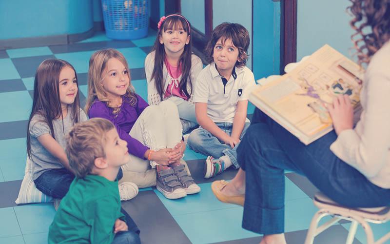 actividad lúdica de niños sentados en círculo escuchando un cuento