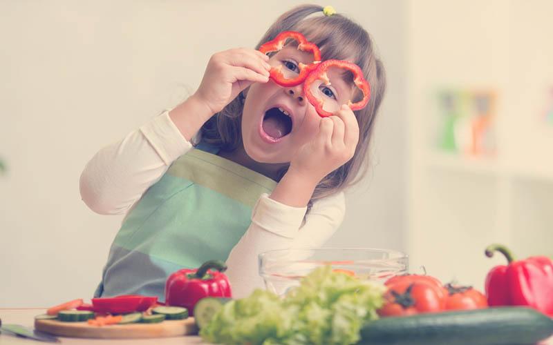 niña cocinando con verduras sonriendo