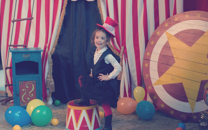 juegos de niña haciendo un dramatizado vestida de sombrero y traje en circo