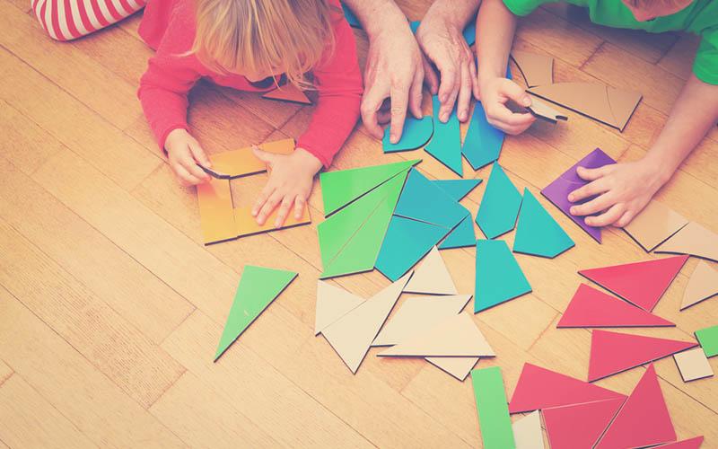 actividad lúdica de niños armando un rompecabezas de colores