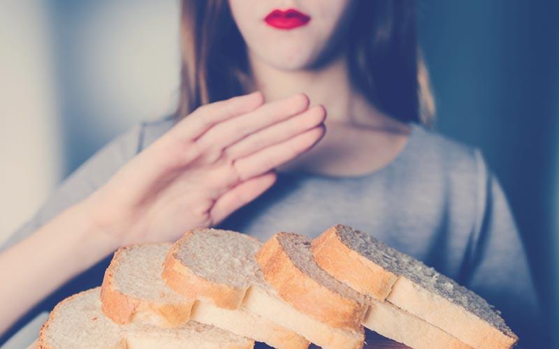 Mujer celíaca evitando comer pan