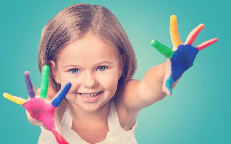 Niño con las manos pintada de muchos colores