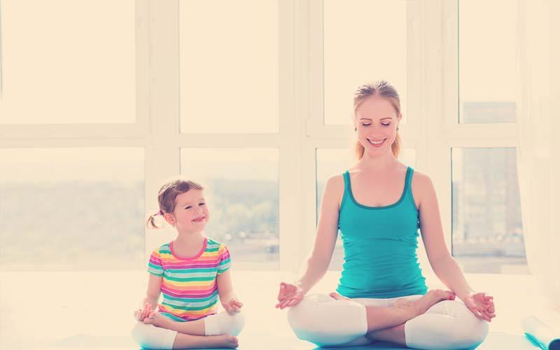 Mamá haciendo yoga con su hija.