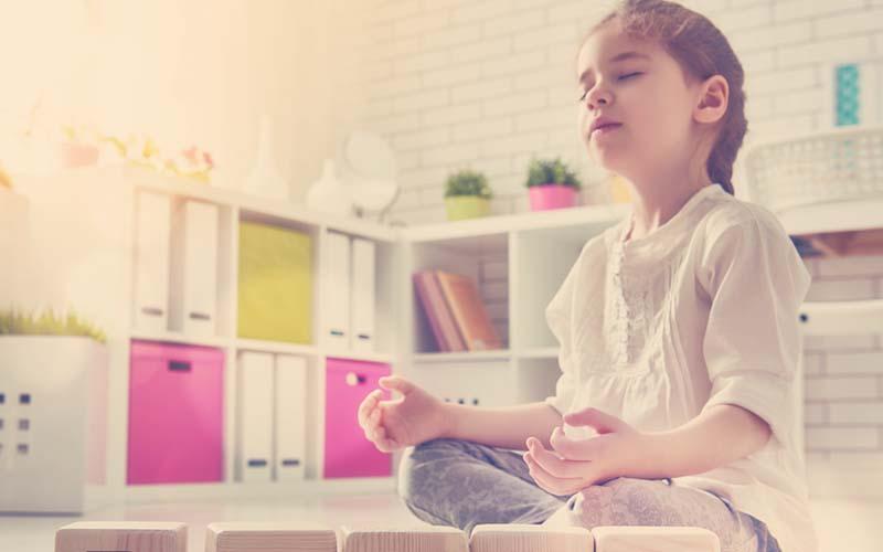 niña meditando en su cuarto