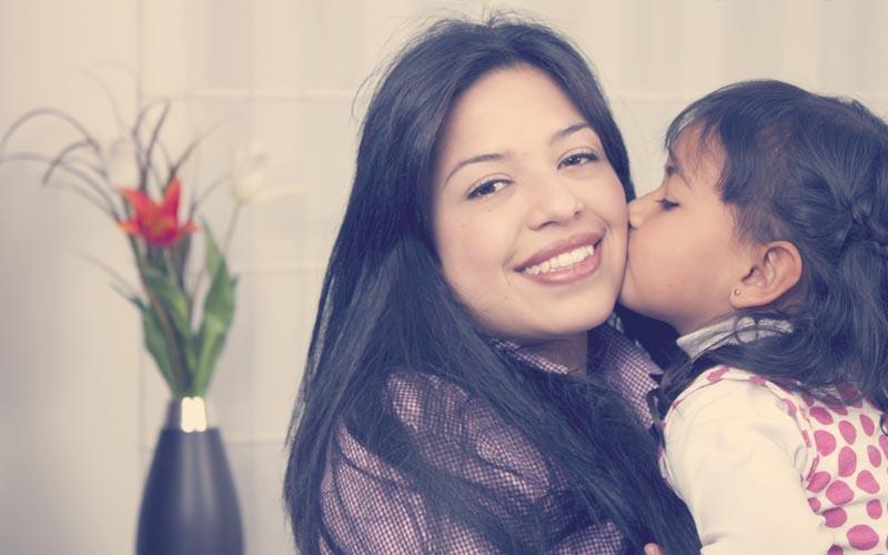 niña besando a su mamá en casa