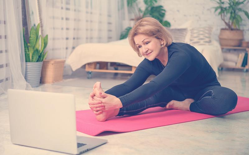 Señora practicando yoga en su casa