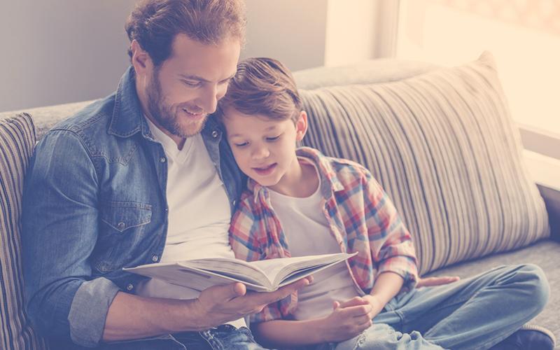 Papá leyendo junto a su hijo un libro, un plan para el dia del padre