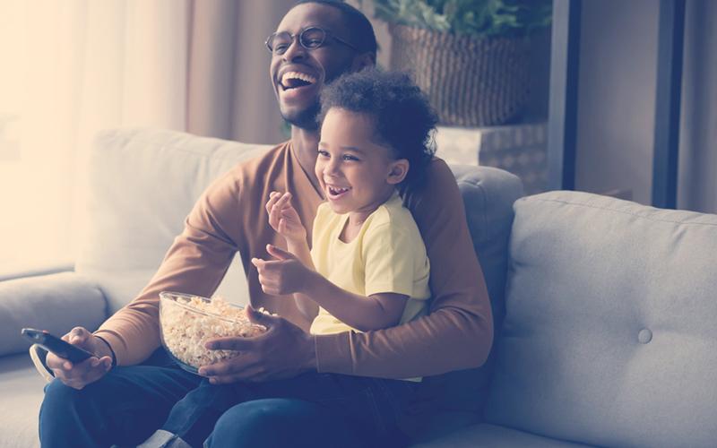 Papa e hijos comiendo palomitas y viendo una películas para papás