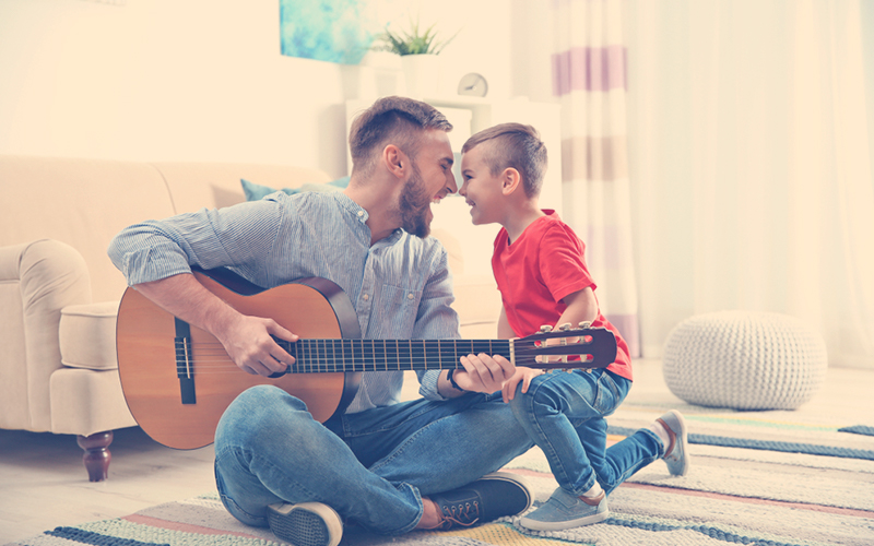 Papa divirtiéndose con su hijo mientras toca la guitarra