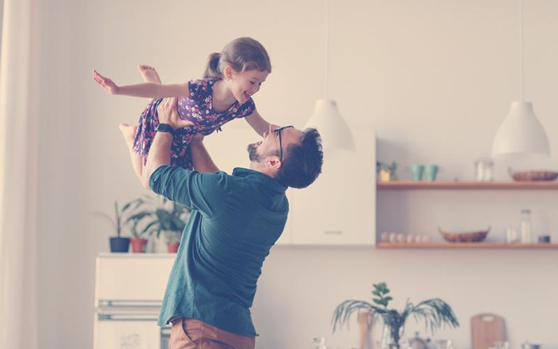 Papá jugando con su hija en el mes del padre