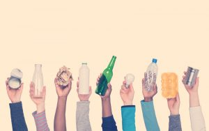 Personas levantando la mano con productos de reciclaje