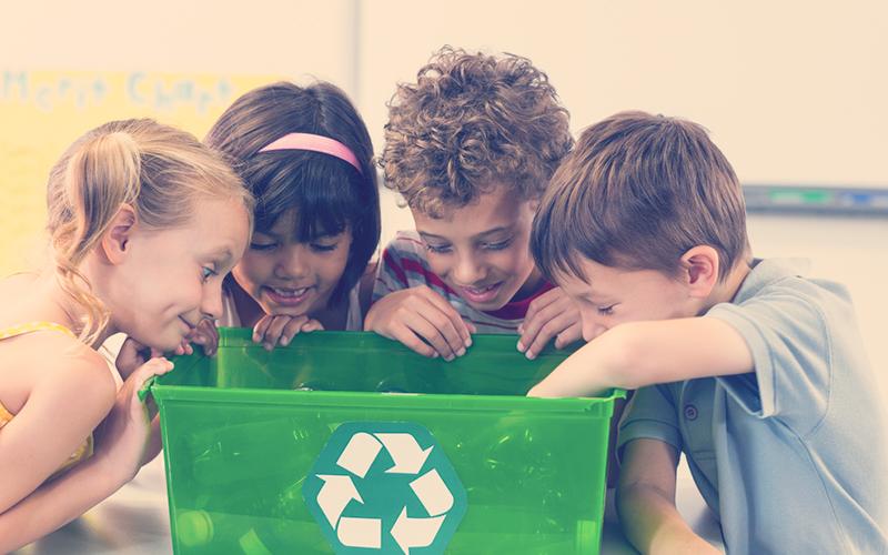 Niños reciclando en una caneca verde