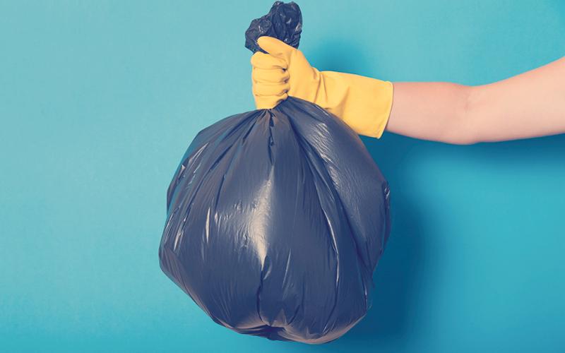 Mujer sacando bolsa negra en la que ha separado sus residuos