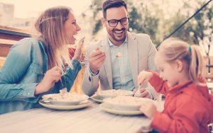 Familia sentados en la mesa comiendo juntos