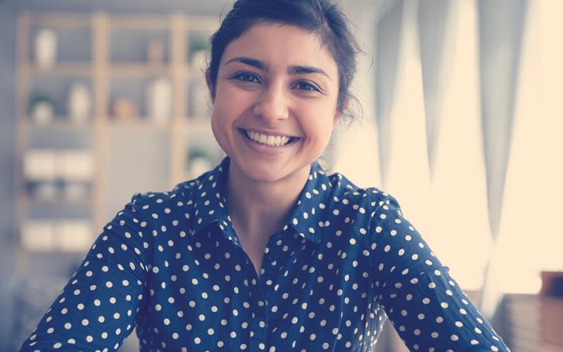 Mujer sonriendo en una videollamada de trabajo