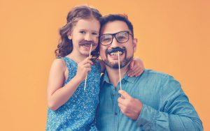 Niña con su papá poniéndose un bigote en su cara