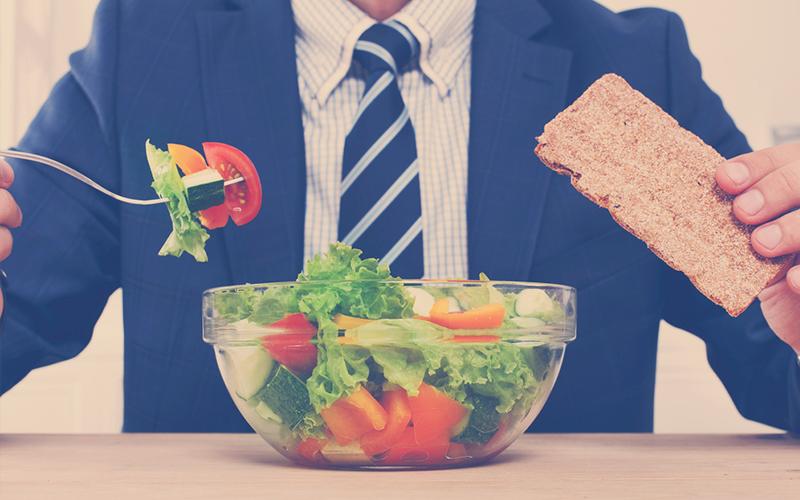 Hombre en traje comiendo verduras