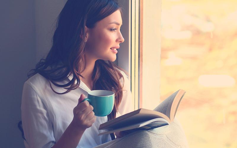 Mujer mirando hacia la ventana pensando en cómo adaptarse al cambio