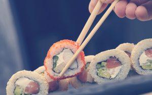 persona utilizando palitos chinos para comer sushi