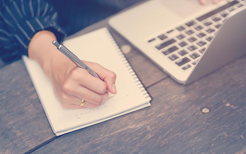 cerrar el contenido de escritura a mano de una mujer de negocios o algo en un ordenador portátil con el uso de una laptop en una mesa de madera fuera de casa, concepto de estilo de vida