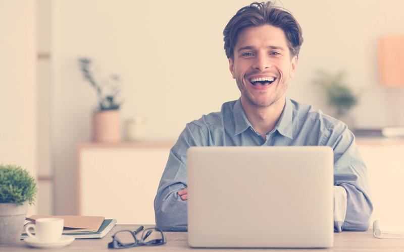 Hombre Sentado En Un Portátil Y Riéndose Mirando La Cámara En El Interior. Espacio vacío para texto
