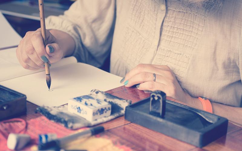 Mujer pintando en una hoja el arte Sumi-e