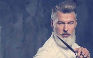 Hombre perfila su barba con unas tijeras