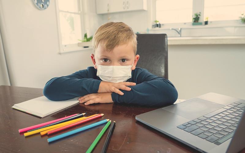 Niño en cuarentena con tapabocas estudiando en su casa