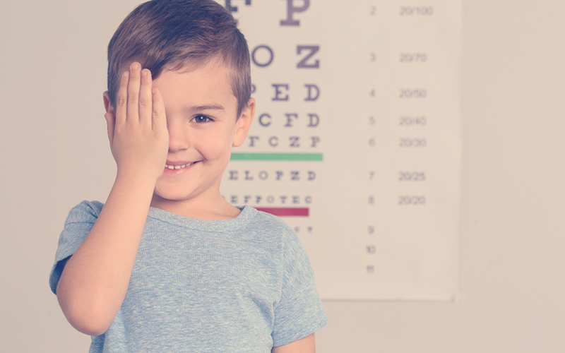 Niño cubriéndose un ojo mientras sonríe para la foto