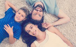 Familia sonríe mientras están acostados en la alfombra