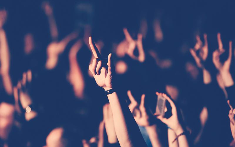 Persona mostrando el signo de los cuernos durante un concierto de banda de rock en el club. Una multitud en un concierto. Dos dedos de mano roca.