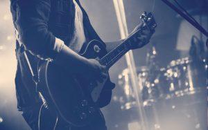 silueta de guitarra en acción en el escenario frente a la multitud de conciertos