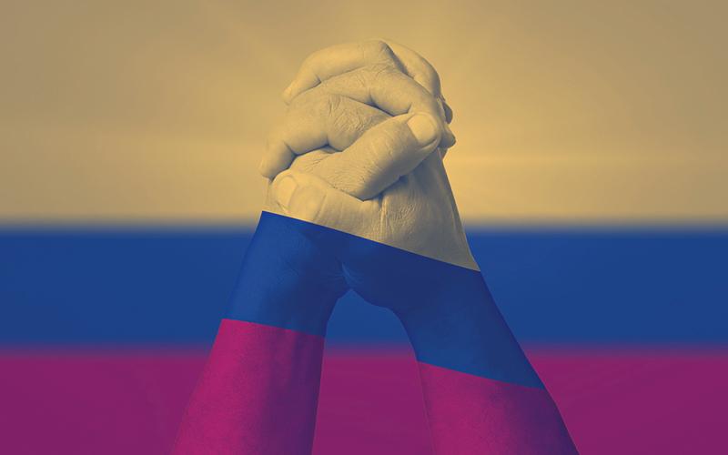 Manos entrelazadas sobre una bandera de Colombia