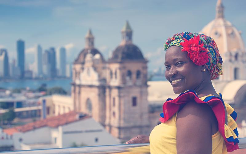 Mujer vestida de forma tradicional con el telón de fondo de Cartagena de Indias, Colombia