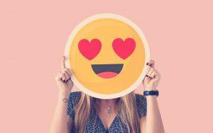 Mujer sosteniendo un emoji corazón ojos cara