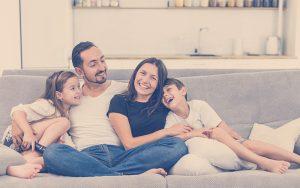 Familia en casa sentados en el sofá teniendo una sana convivencia familiar
