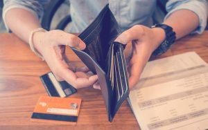 Hombre muestra su billetera y tarjetas de crédito