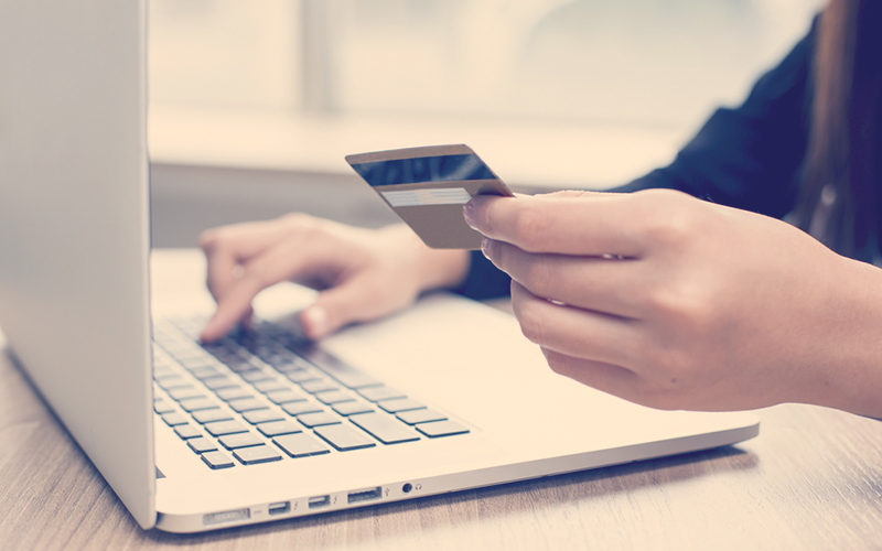 Manos de una mujer pagando con tarjeta de crédito una compra en internet