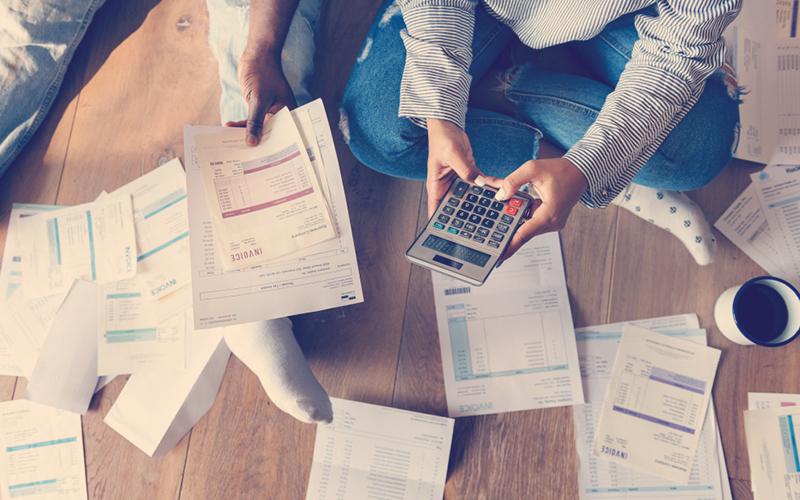 Hombre con calculadora con cuentas en el piso