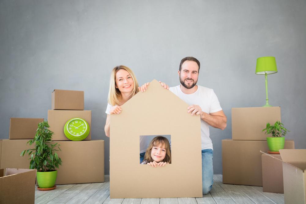 familia jugando a un nuevo hogar. Padre, madre e hijo divirtiéndose juntos. Concepto de mudanzas de día de la casa y propiedad inmobiliaria