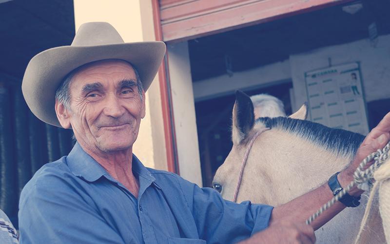 Campesino colombiano junto a un caballo blanco