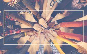 Un grupo de personas poniendo sus manos sobre otras para reflejar unión