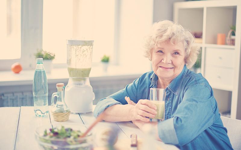 Una mujer mayor tomando un batido saludable